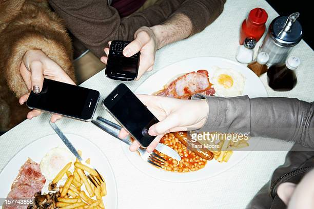 hands holding mobile phones in cafe