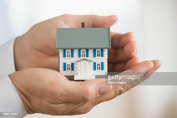 Hands holding model house