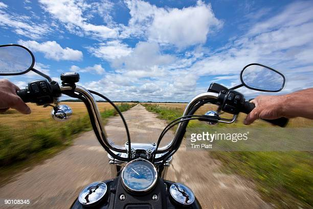 Hands holding motorcycle handlebars.
