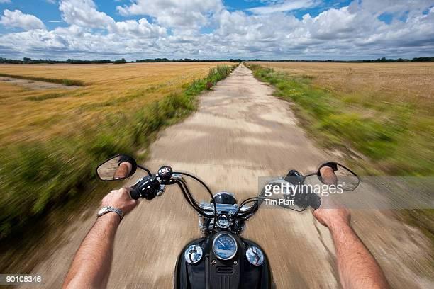 Hands holding motorcycle handlebars.