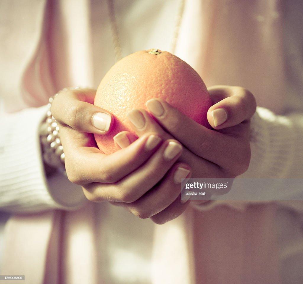 Hands holding orange : Stock Photo