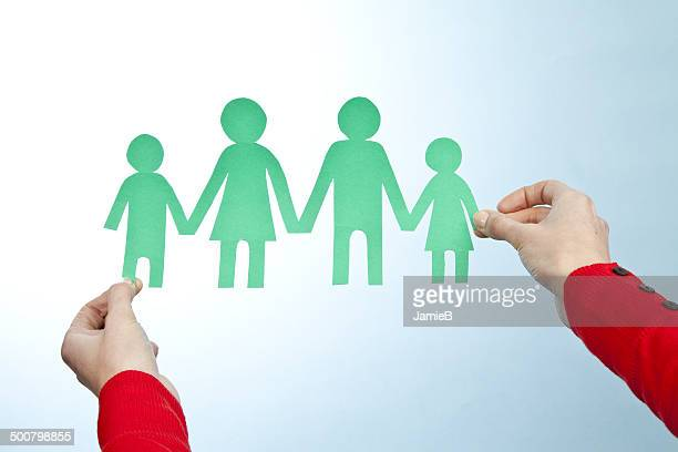 Hands holding paper cut out of family