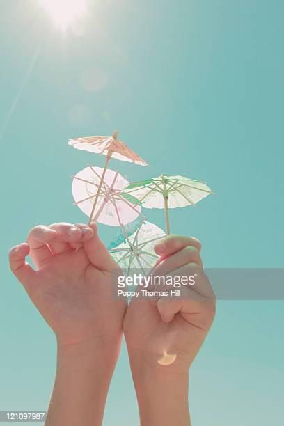 Hands holding paper fairy parasols