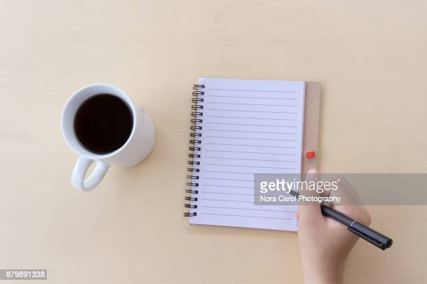 Hands Holding Pen With Open Notepad and Cup of Coffee
