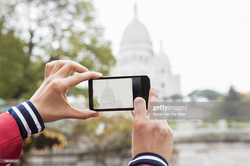 Hands holding phone, making photo of Sacre Coeur. : Stock Photo