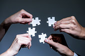 hands holding pieces of jigsaw puzzle, business to business, business matching concept