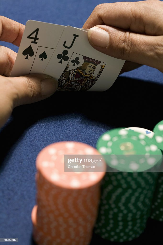 Hands holding playing cards in front of stacks of gambling chips : Stock Photo