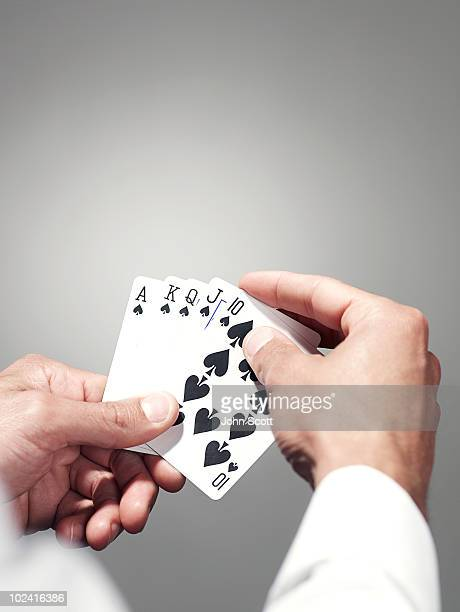 Hands holding playing cards