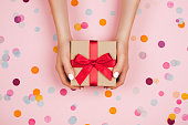 Woman hands holding present box with red bow on pastel pink background with multicolored confetti. Flat lay style.