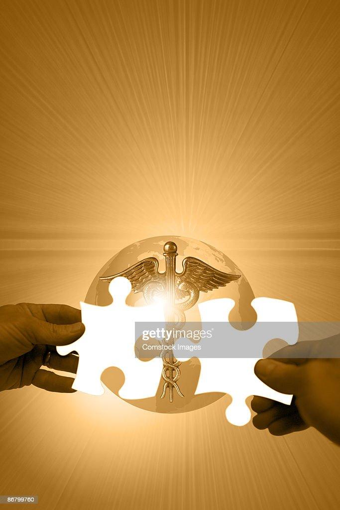 Hands holding puzzle pieces over caduceus