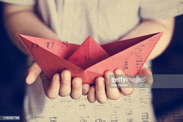 Hands holding red paper boat