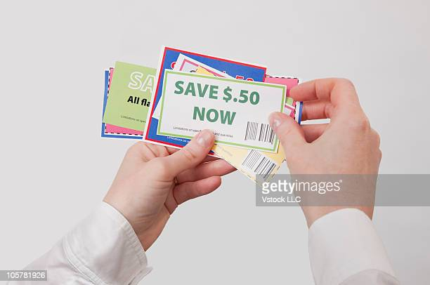 Hands holding shopping coupons