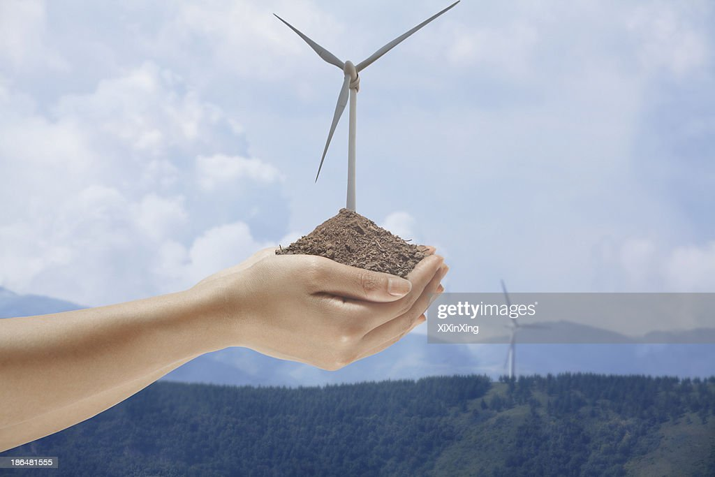Hands holding soil with a wind turbine growing out from the middle : Stock Photo