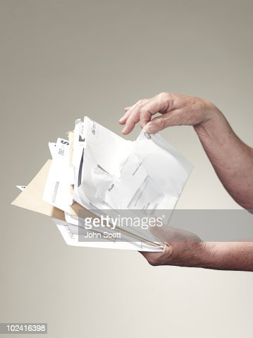 Hands holding stack of letters and bills : Stock Photo