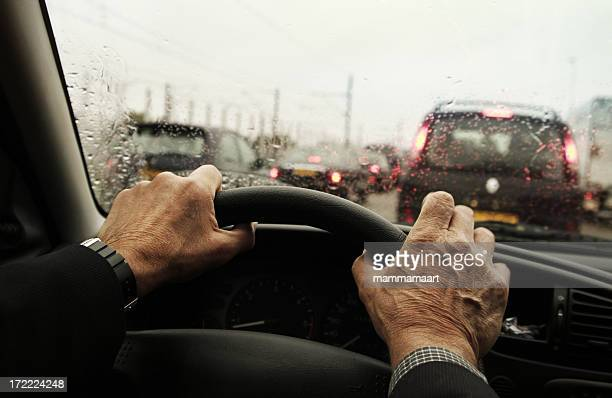Hands holding steering wheel on traffic jam on a rainy day