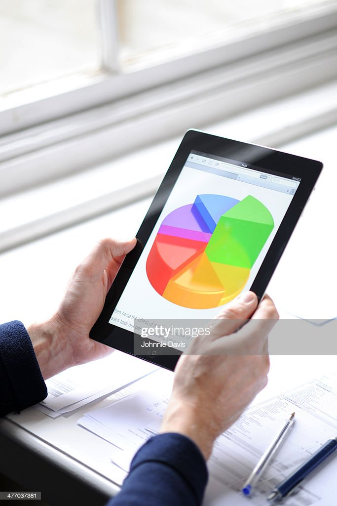 hands holding tablet with pie chart : Stock Photo