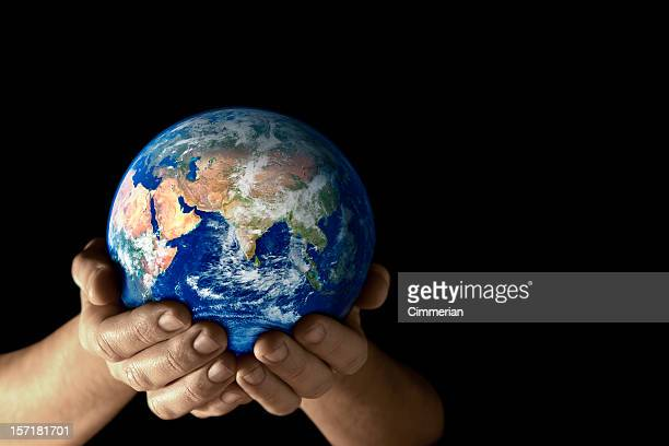 Hands holding the earth facing East on black background