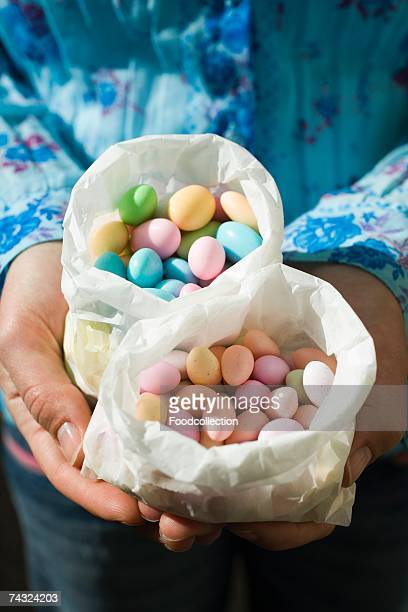 Hands holding two paper bags of Easter sweets