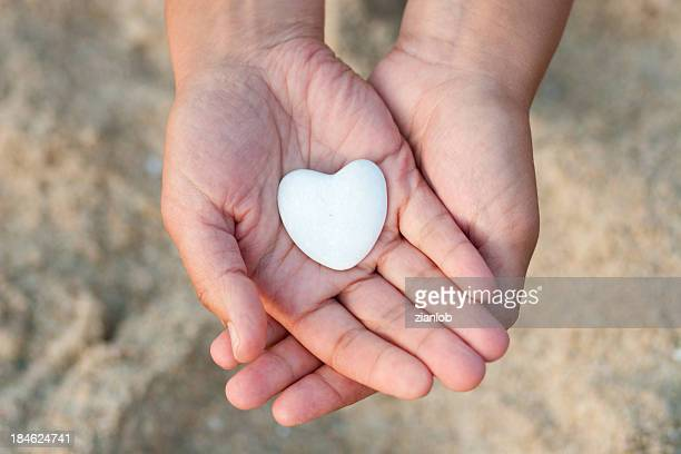 Hands holding white heart-shaped pebble on the beach