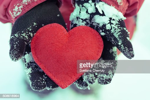 Hands  in dark gloves holding red heart on snowy background : Stock Photo