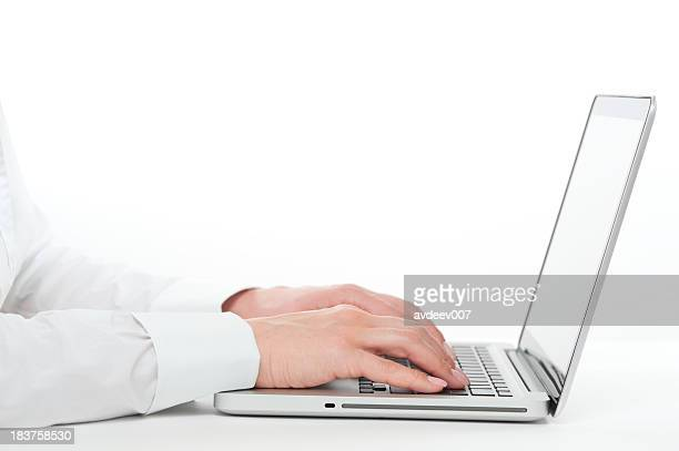 Hands in dress shirt typing on laptop computer