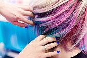 Hairdressers hands in colorful client head and hair after coloring or hair dyeing.