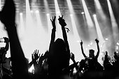 Black and white photo of a girl raising hands while enjoying good music.