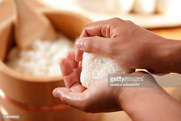 Hands making a rice ball