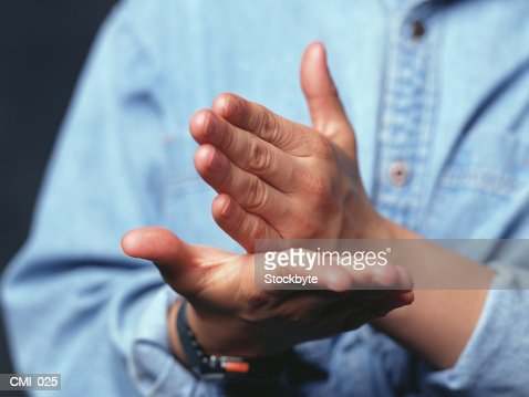Hands making gesture: one hand held straight on open palm of other : Stock Photo