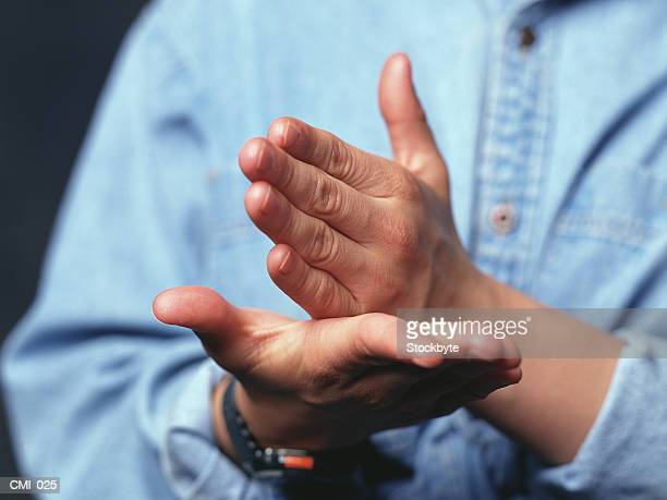 Hands making gesture: one hand held straight on open palm of other