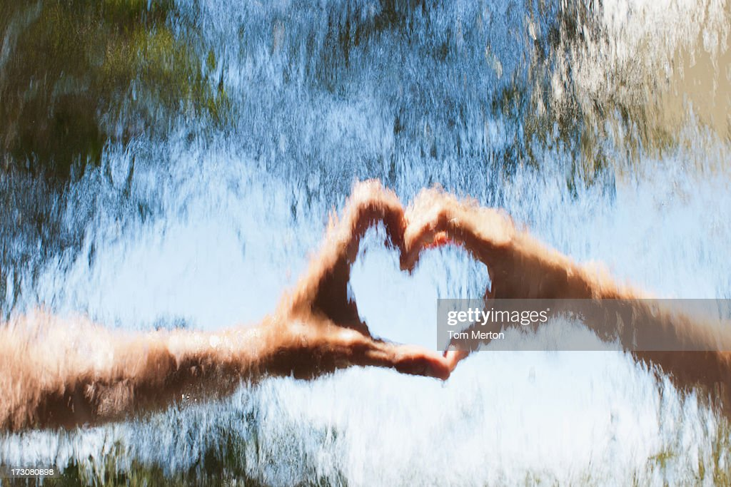 Hands making heart-shape behind glass : Stock Photo