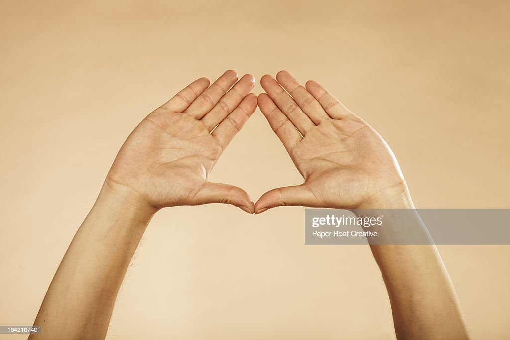 Hands making triangle formation plain background
