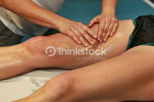 hands massaging athlete's thigh after running : Stock Photo