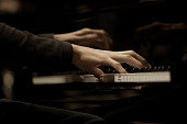 Hands musician playing the piano closeup in dark colors