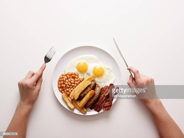 Hands next to plate of fried breakfast