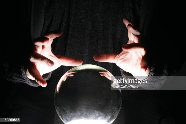 Hands of a black garbed person poised over a crystal ball