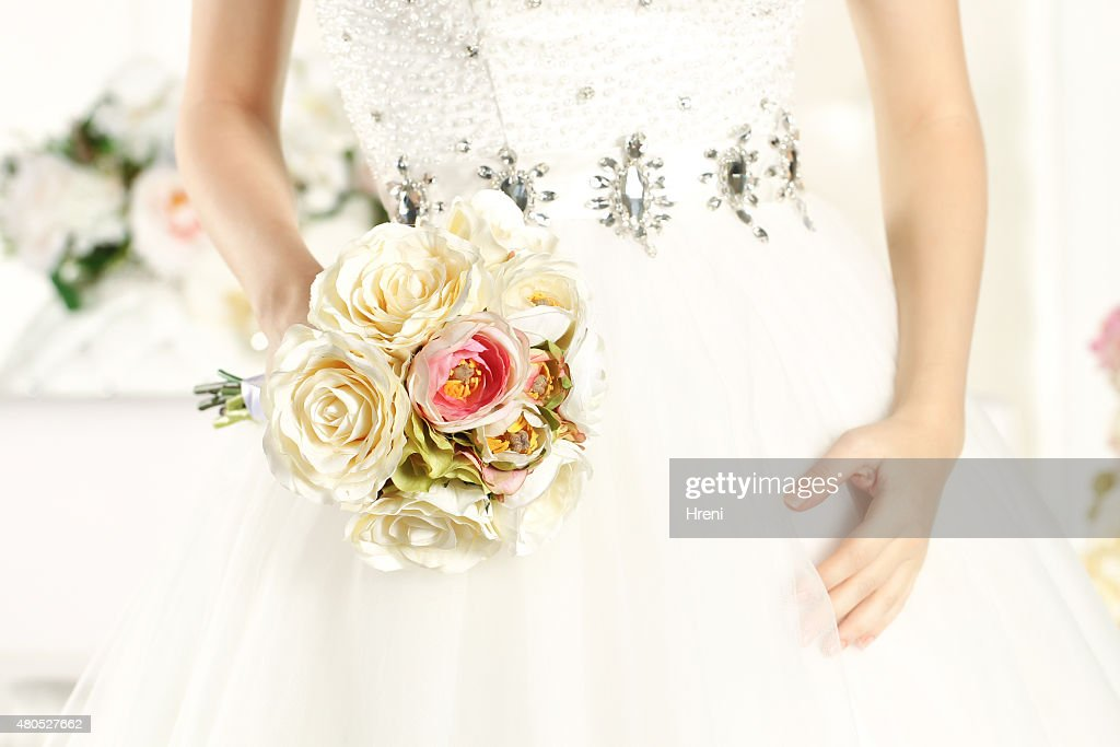 Hands of a bride holding a beautiful bouquet : Stock Photo