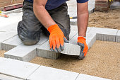 Hands of a builder laying new paving stones carefully placing one in position on a levelled and raked soil base.