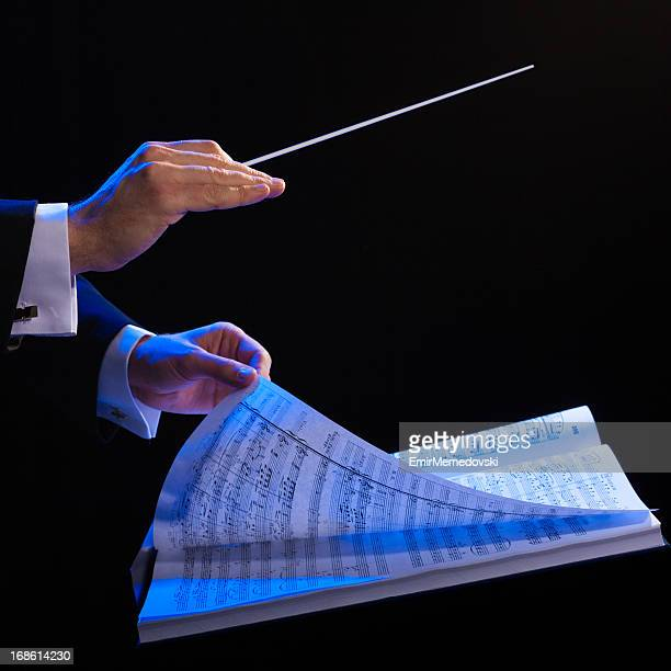 Hands of a conductor with a baton and musical book