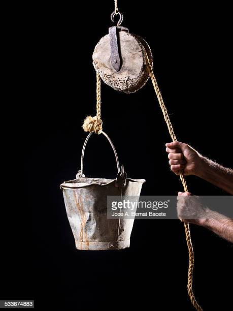 Hands of a man pulling strongly a rope