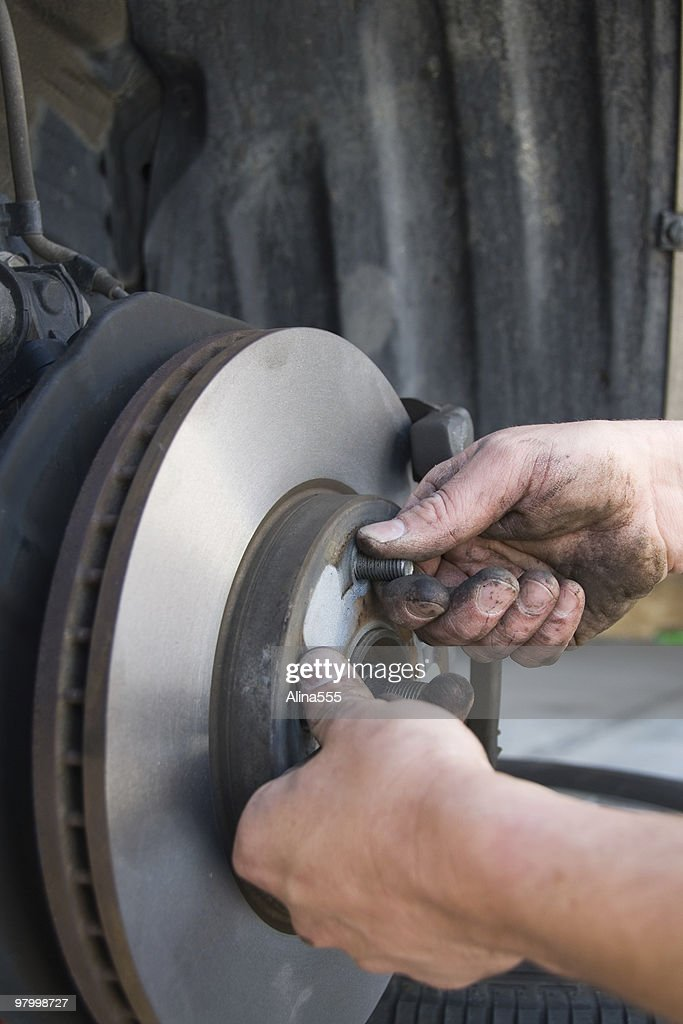 Hands of a mechanic changing brakes