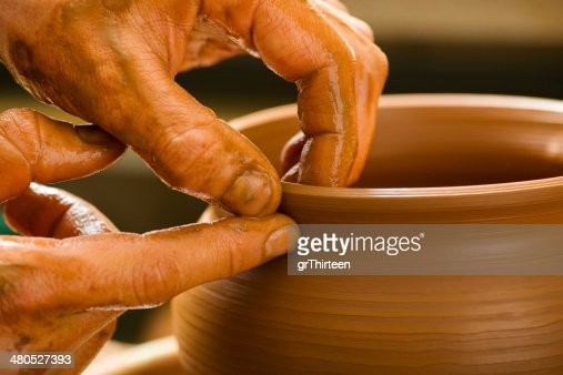 hands of a potter, creating an earthen jar : Stock Photo
