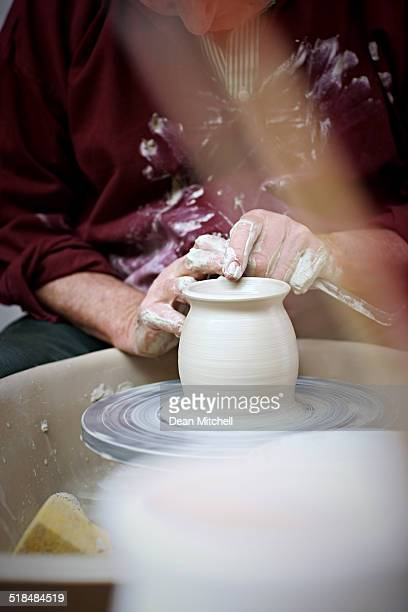 Hands of a potter shaping earthen jar
