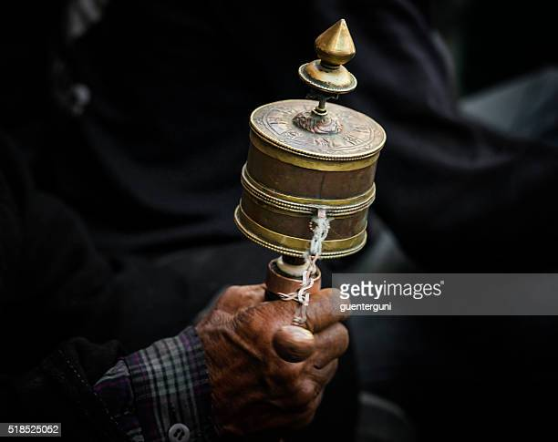 Hands of a Tibetan Buddhist with his prayer wheel