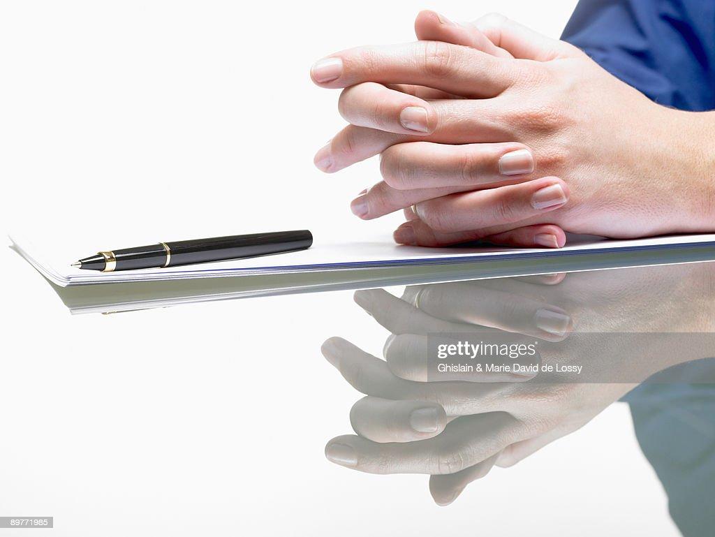 Hands of a woman, resting from writing : Stock Photo