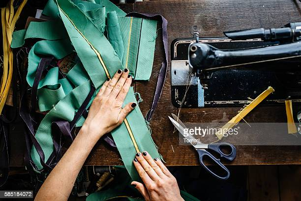 Hands of a woman sewing fabrics