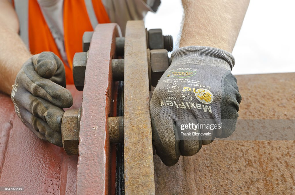 Hands of a worker tightening the bolts of a drain pipe