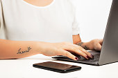 "Hands of a young woman typing on a laptop computer in a close up view with a mobile phone alongside. With ""la reine"" tattoo on arm, meaning "" queen""  in french  with crown sign"