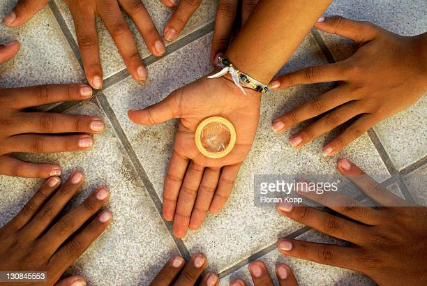 Hands of Adolescents and Comdom