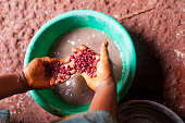 hands of african woman holding red beans view from above in village kitchen while cooking food
